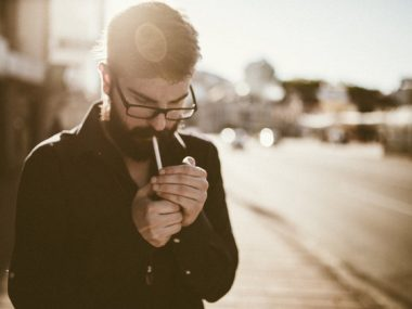 One man, handsome bearded young adult, standing outdoors, lighting a cigarette.