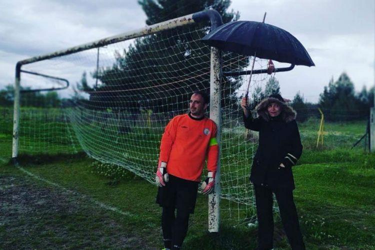 Ελληνίδα μάνα κρατά ομπρέλα στον γιο της σε ποδοσφαιρικό αγώνα