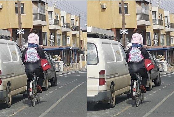 Τύπος οδηγεί το ποδήλατο του (σε κυπριακό δρόμο) και στους ώμους έχει φορτωμένο ένα κοριτσάκι
