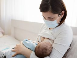 Mother with protective mask breastfeeding her baby sitting on a bed