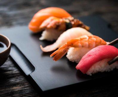 close up of sashimi sushi set with chopsticks and soy on black background